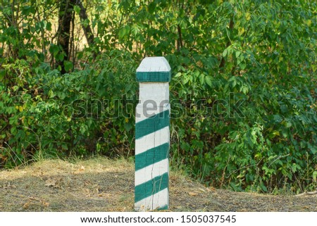 one striped signal pole among the green vegetation in the forest