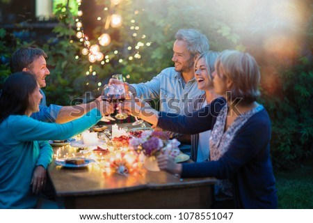 One summer evening, friends in their forties gathered around a table in the garden lit by luminous garlands. They toast with their glasses of wine
