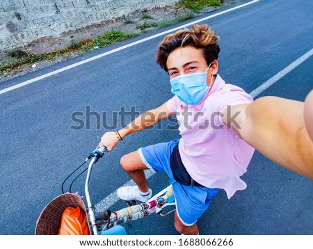 one teenger alone in the middle of the street riding a vintage bike taking a selife and wearing surgical mask to prevent any type of virus or disease like coronavirus or covid-19 - happy people