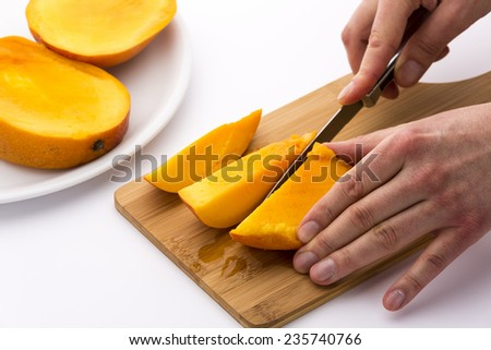 One third of a mango being subdivided into three chips. A left hand is keeping the fruit slice in place on a wooden board, while a right hand is cutting with a kitchen knife. White background.
