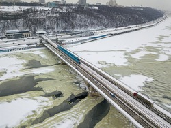 One train on Kiev metro bridge across the frozen Dnieper river. Textured pattern on ice. Aerial drone view. Winter snowy morning.