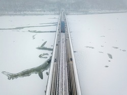 One train on Kiev metro bridge across the frozen Dnieper river. Textured pattern on ice. Aerial drone view. Winter frosty morning.