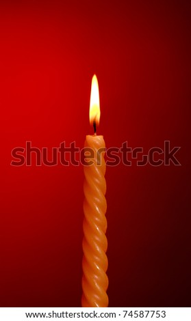 one twisted burning candle over red background