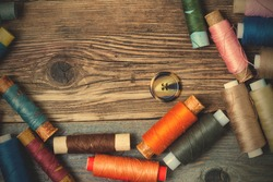 one vintage button and coils of colored threads on the surface of an old tailors table. instagram image filter retro style
