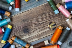 one vintage button and coils of different threads on the surface of an old tailors table