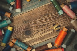 one vintage button and coils of different threads on the surface of an old tailors table. instagram image filter retro style