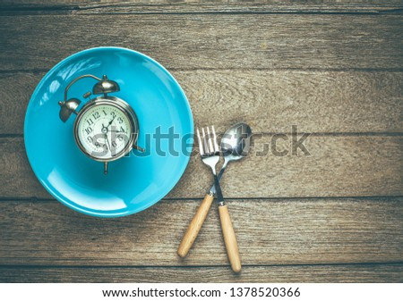 One vintage clock in blue ceramic dish with fork and spoon on wood table top view. Vintage color tone. Free space. #1378520366