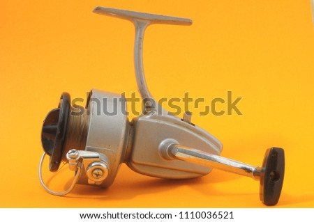One Vintage Old Fishing Reel on a Colored Background