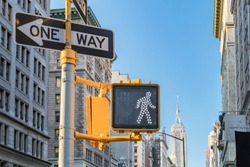 One way and crosswalk signs on a street in Manhattan with the New York City skyline in the background