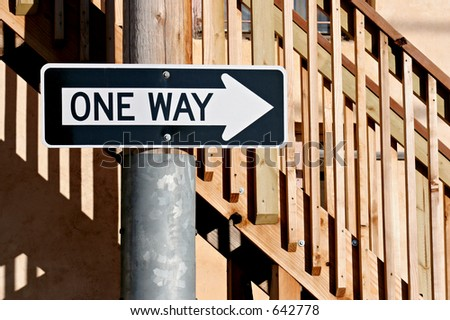 one way sign in front of some stairs in an alley