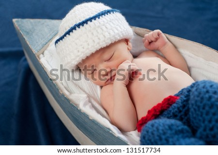 One week old newborn baby boy wearing a white and blue sailor hat. He is sleeping on his back in a tiny boat.