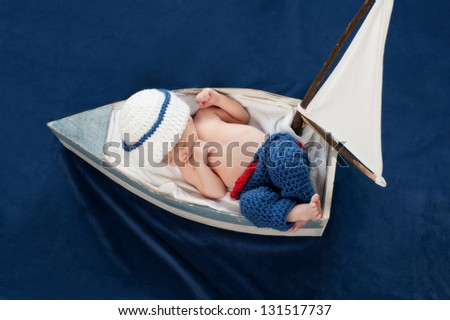 One week old newborn baby boy wearing a white and blue sailor hat. It is an overhead view of him sleeping on his back in a tiny sailboat. Shot in the studio on blue velvet.