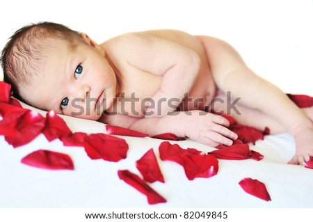 one weeks newborn girl laying with rose petals