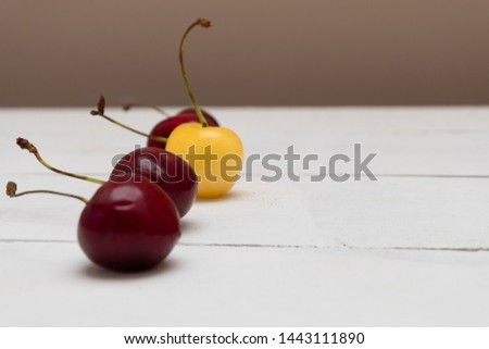 One white cherry standing out from red cherries. Individuality concept