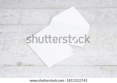 One white greeting card mockup on a white wooden desk. Blank, closed card template with envelope. Perspective angle. ストックフォト ©