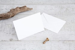 One white greeting card mockup on a white wooden desk. Blank, horizontal, closed card template with driftwood, envelope and sealing wax stamp. Perspective angle.