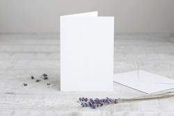 One white greeting card mockup, standing upright on a white wooden desk. Blank, closed card template with envelope.