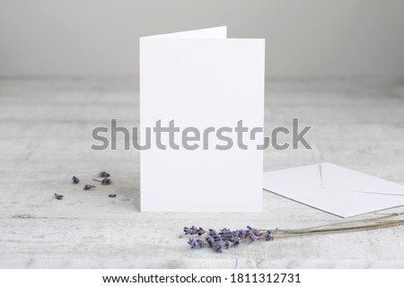 One white greeting card mockup, standing upright on a white wooden desk. Blank, closed card template with envelope.  Foto stock ©