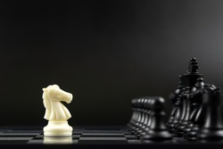 One white knight chess piece facing all black chess pieces for fierce competition situation, one against many concept