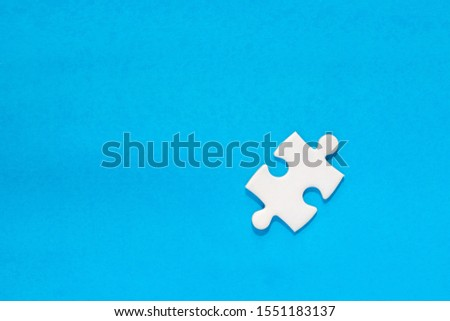 one white painted piece piece of jigsaw puzzle on blue background