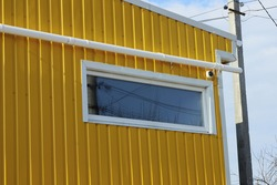 one white rectangular window on a yellow metal wall of a building with a plastic pipe outside