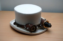 One White Steampunk hat and goggles on a wooden table. Steampunk accessories