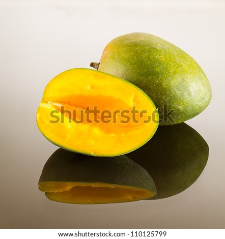 One whole and one cut mango on reflecting glass surface with gradient