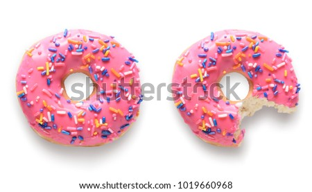 One whole and one with missing bite pink frosted donuts. Isolated on white background