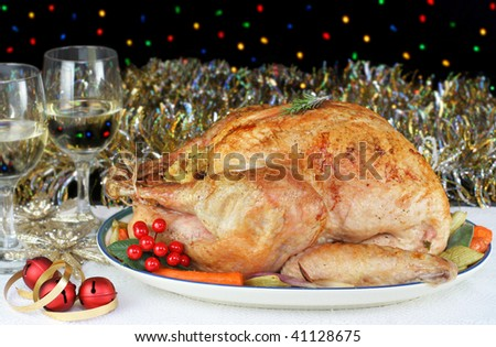 One whole, roasted and stuffed turkey in a Christmas evening setting with bokeh lights in the background.