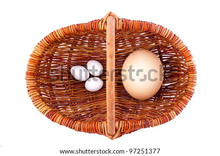 one wicker  basket with ostrich egg and three chicken eggs