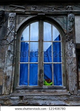 One window in french style in Normandy with blue curtain, old window, aged window, window texture, architecture details close up
