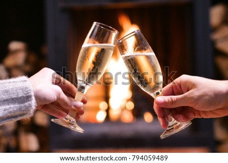 One winter evening a couple sitting in front of the fireplace relaxing, drinking a glass of champagne and making toast to celebrate while enjoying the warmth of the fireplace.  #794059489