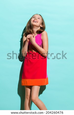 One wish. Happy day dreaming girl in mini dress looking up. Three quarter length studio shot on teal background.