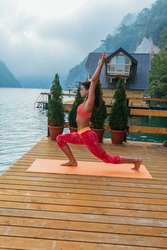 One woman, doing yoga by the lake outdoors alone.
