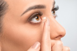 One woman holds contact lens on her finger. Eye care and the choice between the means to improve vision.