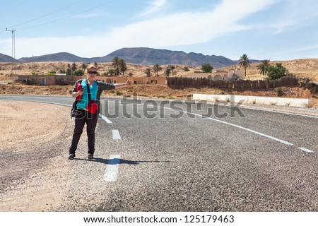 One woman on road with thumb lift up for hitching car