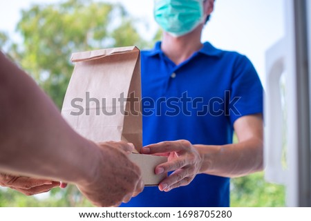 One woman ordered food online to eat at home. The person  orders products or food online, receives parcels from delivery man That put a mask on the door of the house.