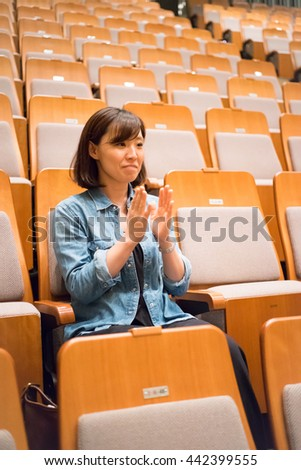 One woman sitting in a chair in the concert hall #442399555