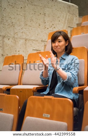 One woman sitting in a chair in the concert hall #442399558