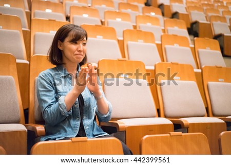 One woman sitting in a chair in the concert hall #442399561