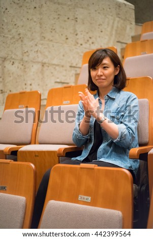 One woman sitting in a chair in the concert hall #442399564