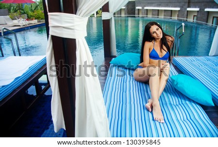 one woman sitting near swimming pool in hotel, bali