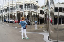 One woman standing on a street in front of a len lye (crooked) mirror and looking to her distorted reflection