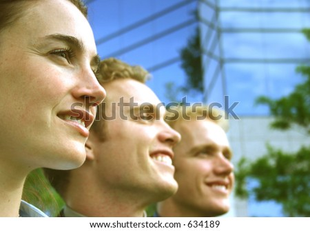 one woman two males profile view in a row smiling with business building exterior