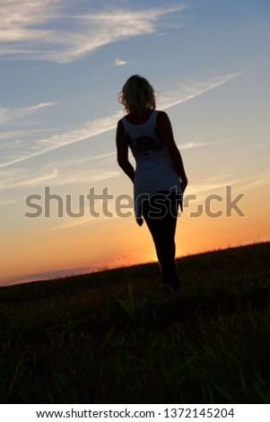 One woman walking in the field in sunset hours. Woman figure, silhouette of young woman on sunset, figure of young woman behind sun in colorful evening background. Romantic evening.Love #1372145204