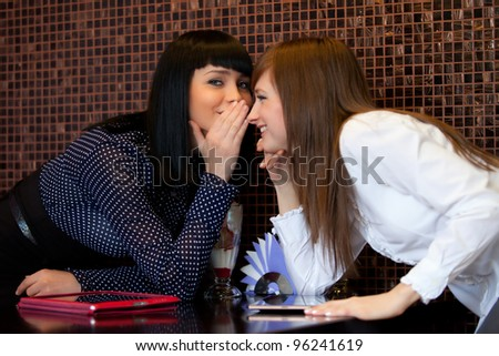 one woman whisper something to friend