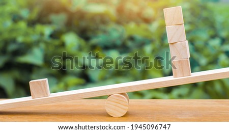 One wooden block on the scales outweighs the other four. Inequality concept. One against the others. Leadership and uniqueness. Unique, dissenting opinion, individual and standing out from the crowd Stock photo ©
