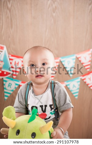 one year baby birthday party. Boy sitting on dinosaurs. Birthday banner behind.Little asian boy celebrating first birthday