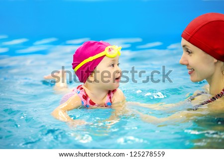 One year  baby girl at his first swimming lesson with mother
