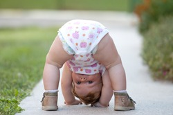 One-year baby girl playing upside down on the street